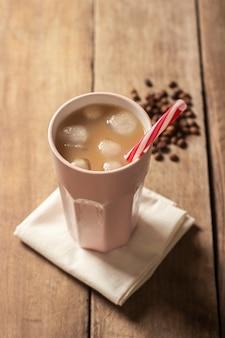 Eiskaffee in einem glas auf einer holzoberfläche erneuernd und aussteifend. konzeptkaffeestube, durst stillend, sommer. flachgelegt, draufsicht