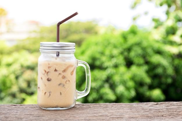 Eiskaffee in einem glas wird auf einen holztisch gestellt.