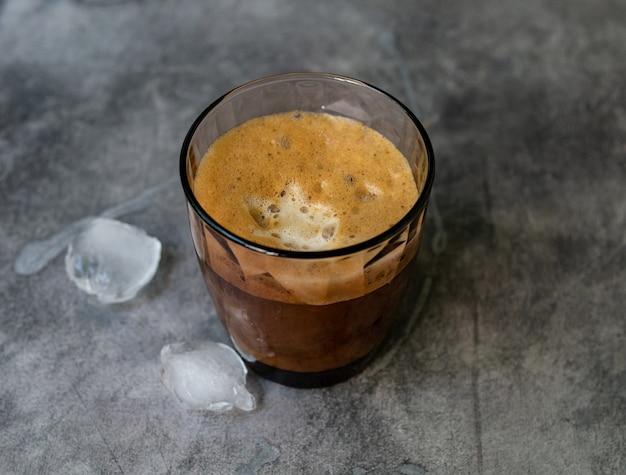 Eiskaffee in einem hohen glas, eiswürfel auf einem grauen holztisch. kaltes sommergetränk mit röhren auf schwarzem hintergrund mit kopierraum. nahansicht.