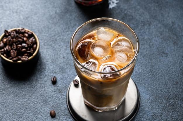 Eiskaffee in einem hohen glas mit sahne übergossen. geeiste latte. kaltes sommergetränk. cold brew im glas. cappuccino auf eis. vietnamesischer eiskaffee.