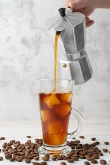 Eiskaffee in glas gießen