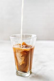 Eiskaffee mit auslaufender milch im glas auf weiß