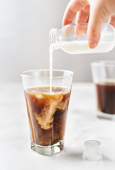 Eiskaffee mit auslaufender milch im glas auf weißem hintergrund