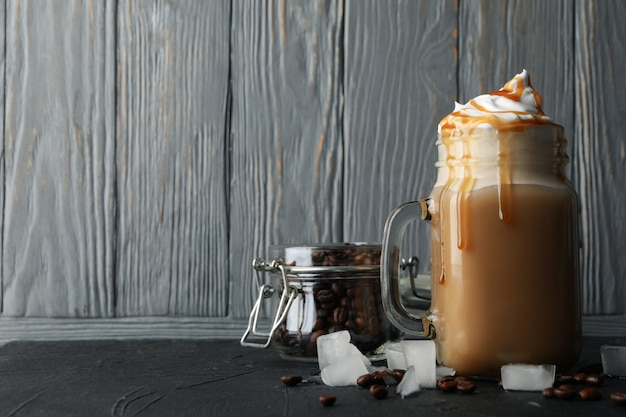 Eiskaffee mit eingegossener sahne auf grauem hölzernem hintergrund