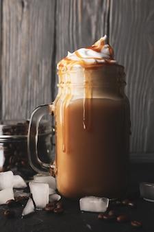 Eiskaffee mit eingegossener sahne auf grauem holz