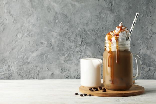 Eiskaffee mit eingegossener sahne auf weißem holzhintergrund