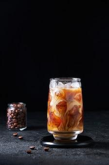 Eiskaffee mit milch im hohen glas auf dunklem hintergrund. konzept erfrischendes sommergetränk.
