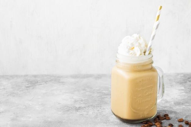Eiskaffee mit milch und sahne auf einem grauen hintergrund. platz kopieren. essen hintergrund