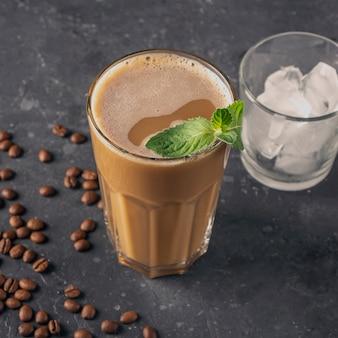 Eiskaffee mit minze und milch. großes glas kaffeecocktail und glas mit eiswürfeln. kühles erfrischungssommergetränk auf dunklem hintergrund im gesetzschlüssel. kopieren sie platz für text.