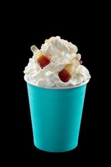 Eiskaffee mit schlagsahne, eis und topping in einem blauen plastikglas auf schwarzem hintergrund