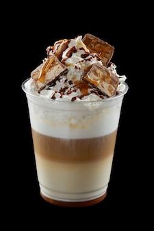 Eiskaffee mit schlagsahne, eis und topping in einem plastikglas auf schwarzem hintergrund