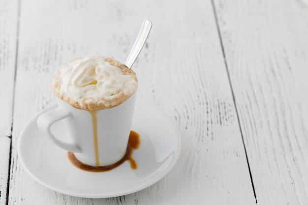 Eiskaffee mit schlagsahne und karamelleis in hohen gläsern auf rustikalem holztisch, selektiver fokus