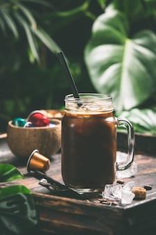 Eiskaffee und tropische blätter, nahaufnahme