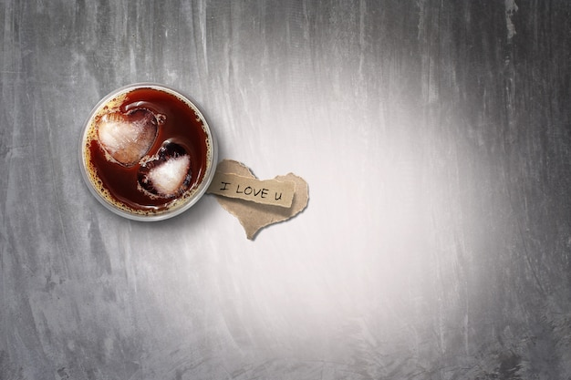 Eiskaffee und zerrissenes papier auf betonboden, farbe getönt. zum valentinstag.