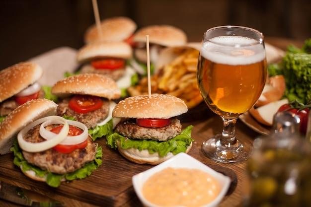 Eiskaltes bier mit leckeren burgern auf einem restauranttisch. gegrilltes fleisch. vintage-restaurant. holztisch.