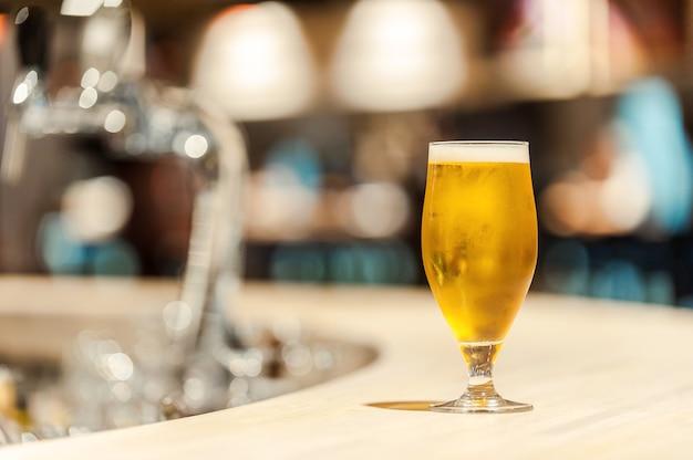 Eiskaltes bier. nahaufnahme von frischem glas bier, das auf der theke steht standing