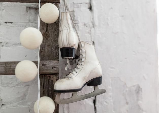 Eiskunstlauf- und weihnachtsgirlandenlichter auf rustikalem hintergrund des alten weißen ziegelsteines