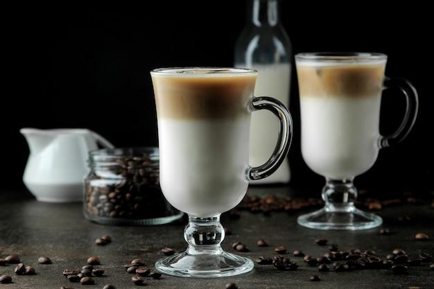 Eislatte oder eiskaffee mit milch und eiswürfeln in einem becherglas vor dunklem hintergrund. erfrischendes getränk. sommer trinken.