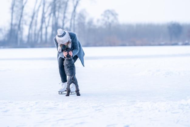 Eislaufen auf dem eis einer jungen attraktiven frau des gefrorenen sees mit hund