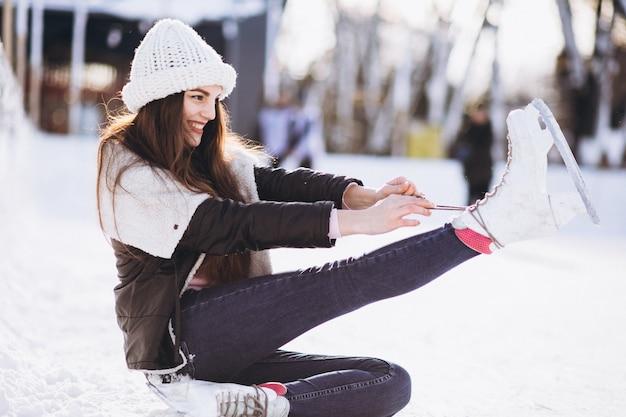 Eislaufen der jungen frau auf einer eisbahn in einem stadtzentrum
