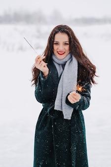 Eislaufen der jungen frau draußen auf einem teich an einem eiskalten wintertag mit wunderkerzen in der hand