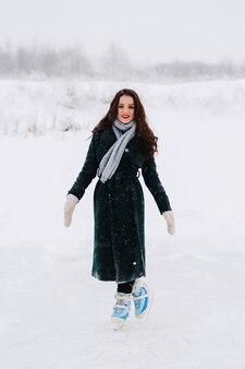 Eislaufen der jungen frau draußen auf einem teich an einem eiskalten wintertag