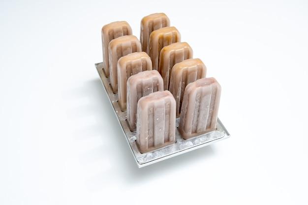 Eislutscher-kaffee in plastikformen auf einem weißen hintergrund mit platz für text. sommerdessert
