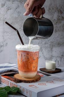Eismilchtee oder thailändischer milchtee in glas auf dem tisch, blasentee herstellen, milchtee in braune zuckermustertrinkglasschale auf weißem holztischhintergrund gießen
