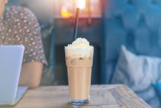 Eismokkakaffee auf holztisch mit dem arbeitsmann, der laptop verwendet