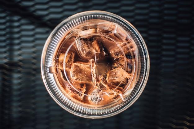 Eisschokolade in einem plastikglas auf schwarzer tabelle.