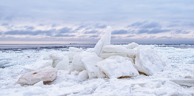 Eisscholle, die gegen küste mit meereis während des eiskalten winterwetters aufbricht. regaleis.