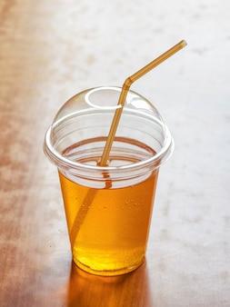 Eistee in einem klaren plastikbecher mit einem strohhalm. kombucha ist ein getränk, das durch fermentieren von tee mit einer symbiotischen bakterienkultur hergestellt wird.