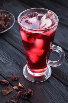Eistee karkade tee im glas auf der schwarzen oberfläche