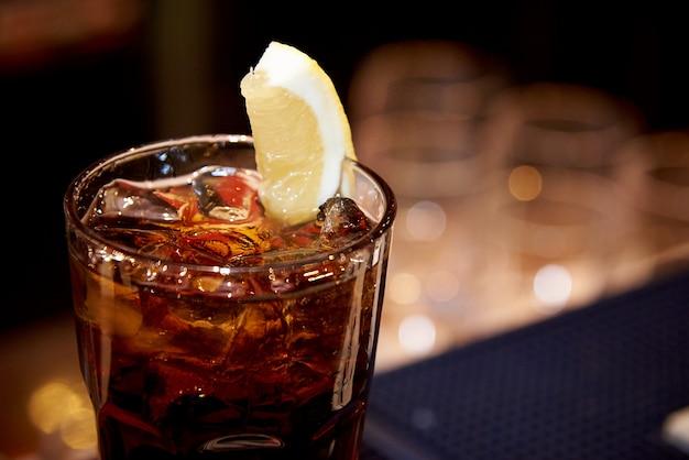 Eistee mit zitrone in einem glas auf einem dunklen unscharfen hintergrund