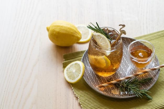 Eistee mit zitrone und honig auf platte, erfrischendes sommergetränk.