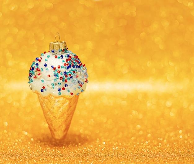 Eistüte auf unscharfem goldenem bokehhintergrund. kopierraum, selektiver fokus. weihnachtsschmuck