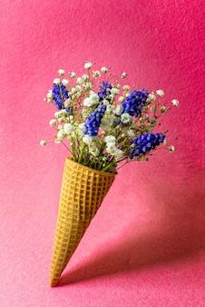 Eistüte mit blumen auf rosa wand. seitenansicht, kopierraum, frühlingsblumenkonzept