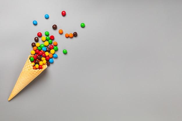 Eistüte mit bunten süßigkeiten auf grauem hintergrund