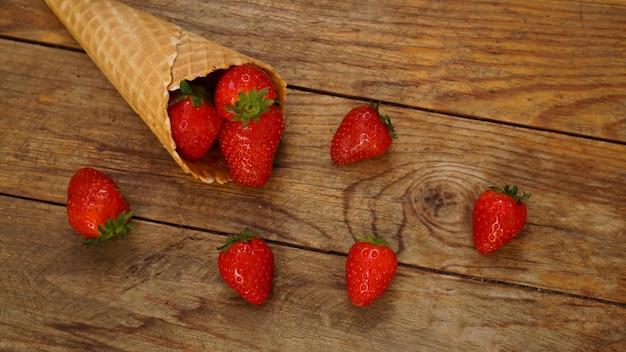 Eistüte mit erdbeeren auf einem hölzernen hintergrund. rote beeren in einem waffelkegel. sommerfoto