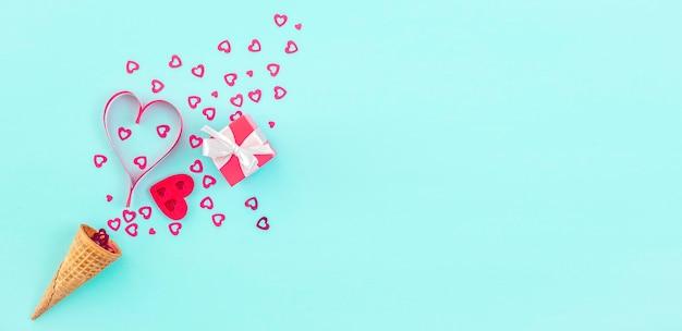 Eistüte mit herzförmiger dekoration und kleiner roter geschenkbox auf blauem hintergrund,