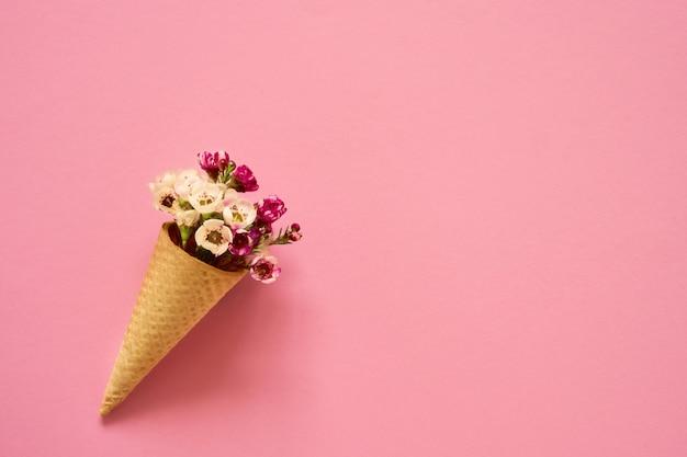 Eistüte mit kleinen blumen auf rosa hintergrund. textfreiraum, ansicht von oben.