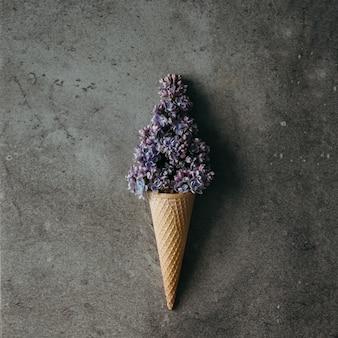 Eistüte mit lila flieder auf marmorwand. flach liegen. sommerkonzept.