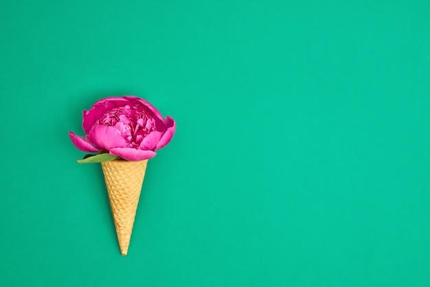 Eistüte mit rosa pfingstrosenblume über grünem hintergrund.