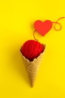 Eistüte mit rotem strickmuster und rotem herzen in der mitte des gelbs