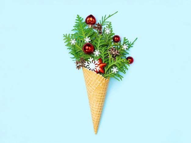 Eistüte mit thuja-zweigen und weihnachtsspielzeug.