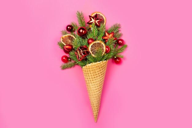Eistüte mit zweigen des weihnachtsbaumes und spielzeug auf einem rosa.
