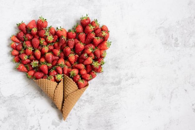 Eistüten in herzform mit frischen erdbeeren
