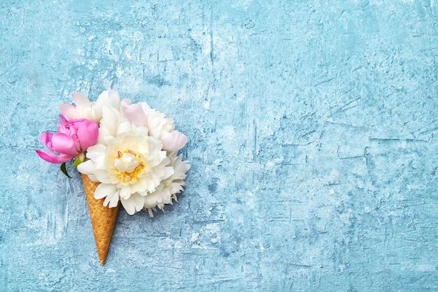Eistüten mit weißen pfingstrosenblüten auf blau. sommerkonzept. speicherplatz kopieren, draufsicht