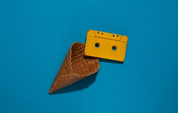 Eiswaffelkegel mit audiokassette auf blauem hellem hintergrund mit tiefem schatten, draufsicht. flach liegend 80er jahre