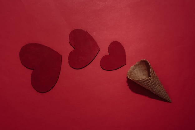 Eiswaffelkegel mit hesrts auf rotem hellem hintergrund. romantische flache lage. ansicht von oben